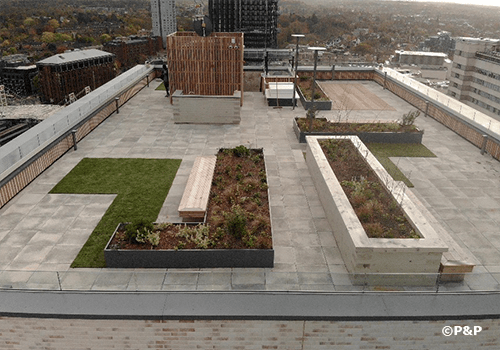 Image shows one of three luxurious roof terraces at Carolyn House, Croydon. Showing planters, paving, decking, slate-top bar etc. all installed by the P&P team.