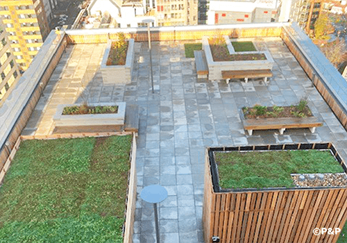The image shows one of the roof terraces at Carolyn House in Croydon, showing planters, paving, decking, slate-top bar etc. all installed by the P&P team.