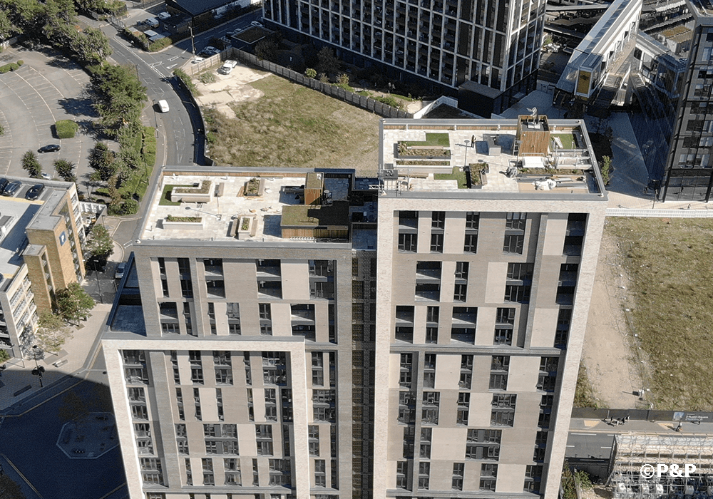 The image shows an aerial photo of the roof terraces at Carolyn House in Croydon, showing planters, paving, decking, slate-top bar etc. all installed by the P&P team.