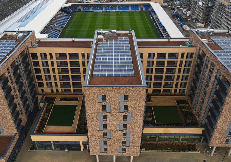 Image shows: aerial shot of roofs of completed block and the AFC Wimbledon pitch